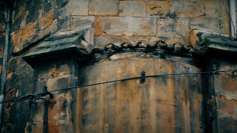 Old wall of abandoned gothic building with shabby roof and barred dirty window Footage