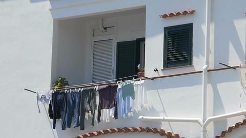 Family laundry drying on balcony of tidy apartment building, establishing shot Footage