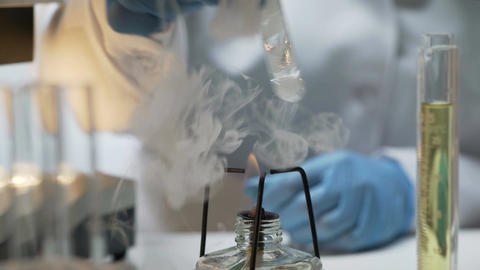 Laboratory assistant heating test tube with biomaterial over burner, research Footage