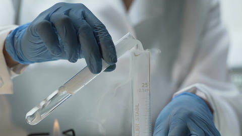 Lab researcher pouring experimental substance into tube, chemistry lesson Footage