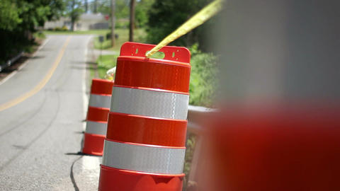 A row of construction barrels on the side of the road with yellow caution tape Footage