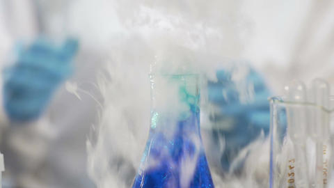 Blue liquid boiling and fuming in flask, chemistry student doing research Footage
