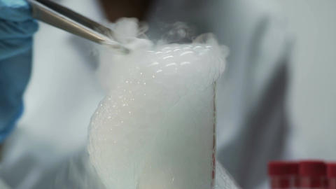 Scientist putting dry ice into neck of flask with thick bubble foam coming out Footage