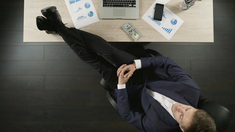 Relaxed wealthy businessman counting money, sitting with feet on table, top view Footage