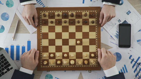 Company leaders playing chess, using business strategy to win market, top view Footage