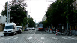 urban street with passing cars and trams and buildings - people walking - road r Footage