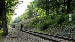 man runs across the rails - the track for the train in the forest - trees Footage