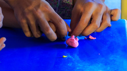 kid's and mother's hands sculpture pink toy pig of plasticine Footage