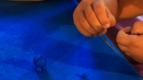 kid's hands sculpture toy animal of blue plasticine Footage