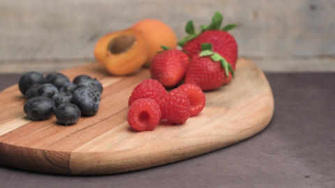 Wooden board with fresh organic fruit and berries Footage