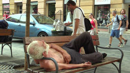 Authentic homeless man looking from the trash bin and homeless man asleep on a Footage