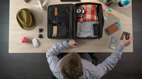 Man carefully packing suitcase for travel, taking money and documents, top view Footage
