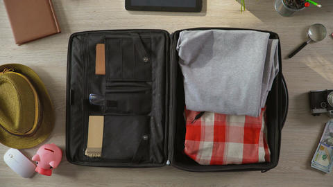 Animated things quickly filling suitcase, bag leaving room, top view stop-motion Footage
