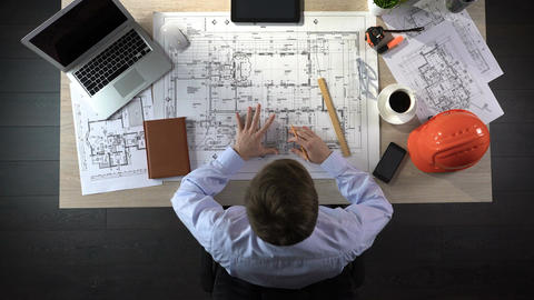 Engineer nervously checking drawings before beginning of building construction Footage