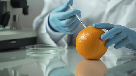 Cosmetologist extracting essential oils from orange, citrus vitamin products Footage