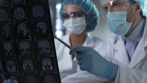 Neurosurgeon showing human MRI scan and giving explanation to medical intern Footage