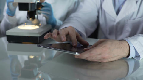 Male scientist scrolling tablet screen, colleague working with microscope nearby Footage