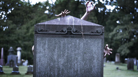 Moody horror movie concept - Zombie hands reaching around giant tombstone Footage