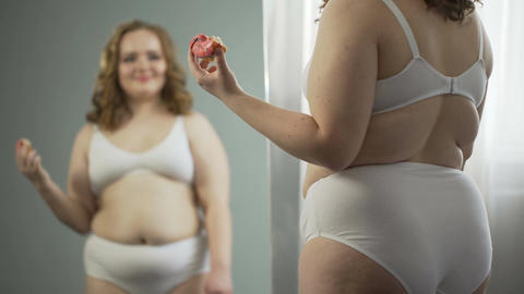 Fat lady in underwear looking at her mirror reflection and enjoying sweet donut Footage