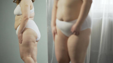 Girl examining in mirror her sagging cellulite body, pondering about surgery Footage