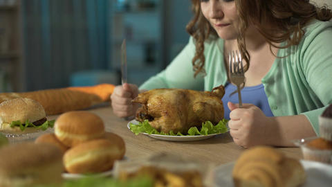 Female sharpening knife against fork over roast chicken, getting ready to eat it Footage