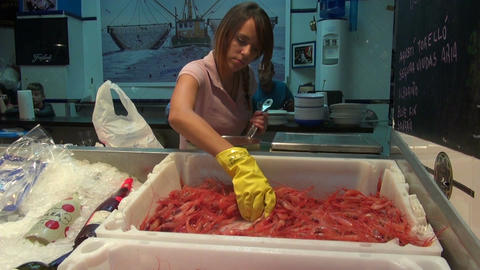 saleswoman and fresh and boiled shrimps prawns in plastic box for sale on fish m Footage