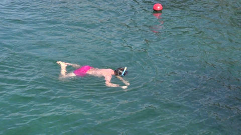 Child wearing pink swimming trunks snorkeling in sea Footage
