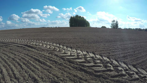 Freshly plowed farm field in autumn with tractor traces and clouds. Time lapse 4 Footage