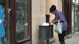 Authentic homeless woman looking and eats food from the trash bin Archivo
