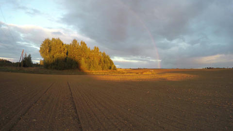 evening rainbow over plowed field and sunset shadows. Time lapse 4K Footage