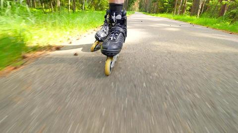 Outdoor shuffle inline skating. Mans legs roller skating on forest asphalt path. Footage
