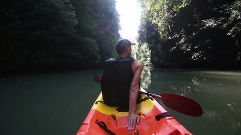 old man drifts on kayak down calm river rests looks around Footage