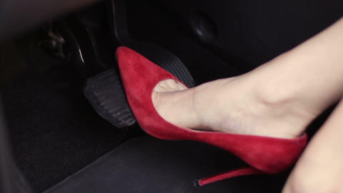 Woman in red high heels shoes pressing car pedals Footage