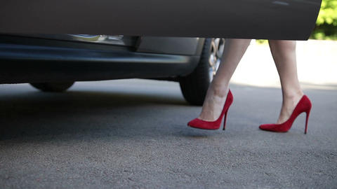 Elegant female legs in red heels getting into car Footage
