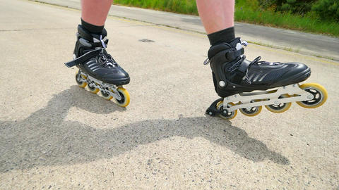 Roller skating and heel braking on the asphalt. Close up view to quick movement  Footage