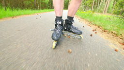 Start inline skating on smooth asphalt in the forest. Close up view to light ski Footage