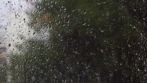 Raindrops falling on glass window with blurred green nature background Footage