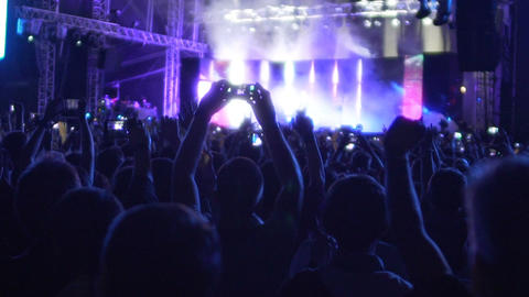 Happy audience jumping and raising their hands to air at rock group concert Footage