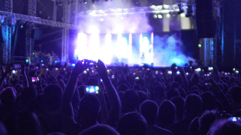Devoted fans filming favorite band performance on mobile phones, saving memories Footage