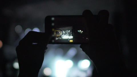 Person filming live performance of beloved rock band on smartphone camera Footage