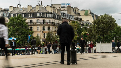 Square crowded by people with suitcases walking around during day, time-lapse Footage
