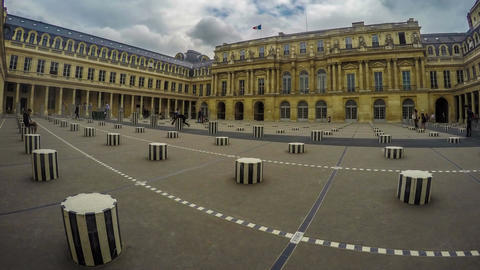 People moving among black and white columns in Royal Palace courtyard in Paris Footage
