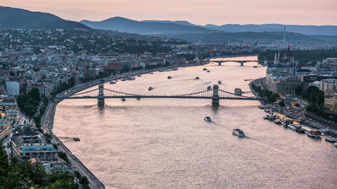 Pleasure boats sailing down Danube River under bridges, day-to-night time-lapse Footage