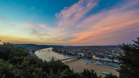 Aerial view of Budapest and Danube River with ships under glowing sky at dusk Footage