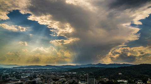 Sunrays penetrating clouds in heavenly sky above mountain resort city, timelapse Footage