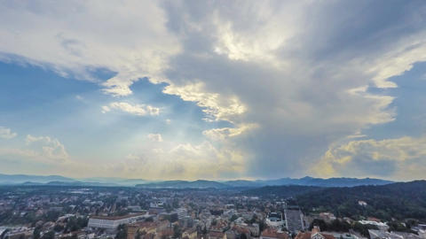 Clouds floating in blue sky over city with sunbeams penetrating them, timelapse Footage