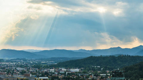 Sunrays shining through clouds over city surrounded by mountains, time-lapse Footage