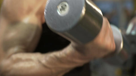 Male lifting heavy dumbbells with both hands simultaneously, close-up of arms Footage