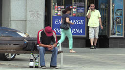 Street life, man senior sitting on a bench and another man on the phone, on the Footage