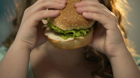 Fat girl holding fast food burger with both hands and chewing it, face closeup Live Action